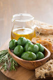 Fresh green olives, olive oil and ciabatta on wooden board Stock Photos