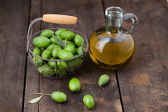 Fresh green olives. With olive oil on wooden table Stock Photo