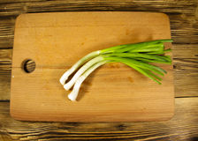 Fresh green onion on cutting board on wooden table Stock Photos