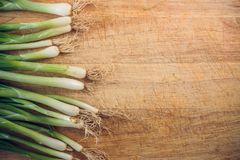 Fresh green onions lying on a wooden chopping Board. the view from the top stock photos