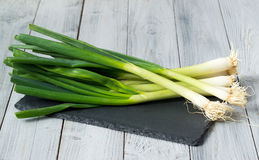 Fresh green onions on the slate cutting board, wooden background Stock Photos