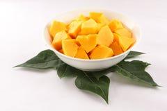 Fresh green papaya leaf with organic papaya fruit slices. Royalty Free Stock Photos