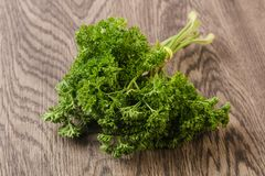 Fresh green parsley. Heap over the wooden background Royalty Free Stock Photos