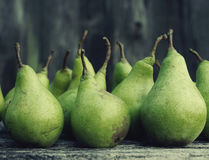 Fresh green pears against an old textural wooden surface. Royalty Free Stock Photo