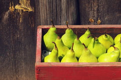 Fresh green pears in a red wooden box. Stock Photos