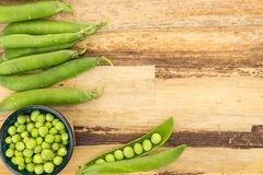 Fresh green peas in bowl and pea pods Stock Photo