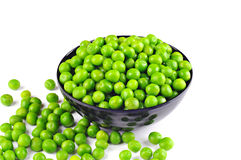 Fresh green peas in a bowl, on the table, on white background. Fresh green peas in a black bowl, on the table, on white background Stock Photo