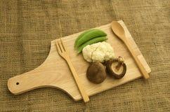 Fresh green peas,cabbage and shitake mushroom on wood cutting bo Stock Photography