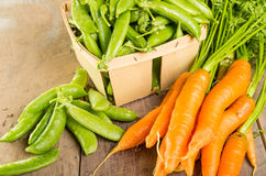 Fresh green peas and carrots Royalty Free Stock Photography