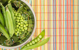 Fresh green peas in colander, on colorful placemat. Fresh green peas in colander, on colorful bamboo placemat Stock Photo