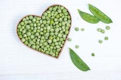 Fresh green peas in heart shape Royalty Free Stock Image