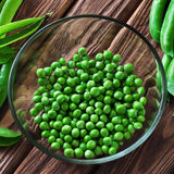 Fresh green peas peeled in a glass bowl Royalty Free Stock Photos