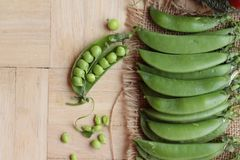 Fresh green peas pod on wood background. Stock Photos