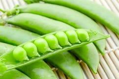 Fresh green peas pods. Fresh green peas pods on bamboo mat background Stock Image