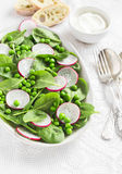 Fresh green peas, spinach and radish salad on a ceramic oval plate Royalty Free Stock Photography