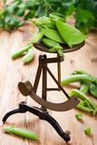 Fresh green peas on vintage scales Stock Photo