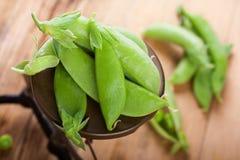 Fresh green peas on vintage scales Stock Photos