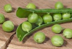 Fresh green peas on wood cutting board Stock Photo