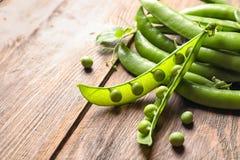 Fresh green peas on wooden background,. Closeup Stock Photo