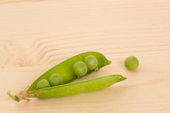 Fresh green peas on a wooden table Stock Image