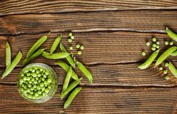Fresh green peas on a wooden table. Top view Stock Photo