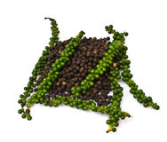 Fresh green peper on heap of Black Pepper Stock Image