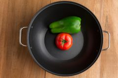 Fresh Green peper and tomato in a black bowl on the rustic wood table royalty free stock photos