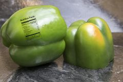 Fresh green pepper with nutrition label. Fresh whole sweet green peppers on black tile with nutrition label Stock Photography