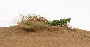 Fresh green pepper, piper nigrum, spice falling in pepper ground on white background, slow motion. 4K stock footage