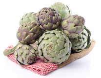 Fresh green purple artichokes on burlap. Isolated on white Stock Images