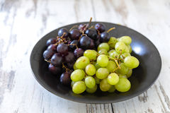 Fresh green and purple grapes in a bowl on white painted wood Royalty Free Stock Image
