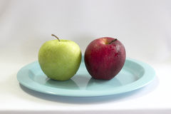 Fresh green & red apple on blue plate. Stock Photography