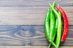 A fresh Green and Red chilli on wooden background. A fresh green and red chili on table Royalty Free Stock Photo