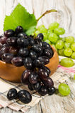 Fresh green and red grapes in a wooden bowl Royalty Free Stock Photo