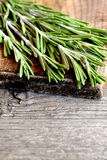 Fresh green rosemary sprigs on a cutting board and an old wooden background with blank space for text. Closeup. Fragrant herb used in cooking, medicine Stock Photo