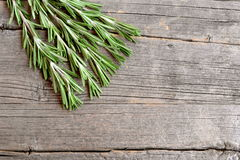 Fresh green rosemary sprigs on a kitchen board and an old wooden background with empty copy space for text. Fragrant herb used in cooking, medicine, cosmetics Royalty Free Stock Image