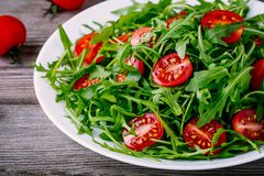 Fresh green salad with arugula and red tomatoes on wooden background Stock Photos