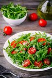 Fresh green salad with arugula and red tomatoes on wooden background Royalty Free Stock Photography
