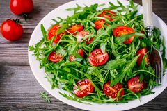 Fresh green salad with arugula and red tomatoes on wooden background Stock Image