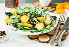 Fresh green salad with arugula, yellow tomatoes, olives, grapes. And sesame,healthy lifestyle and raw food concept Royalty Free Stock Image