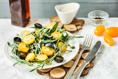 Fresh green salad with arugula, yellow tomatoes, olives, grapes Royalty Free Stock Image