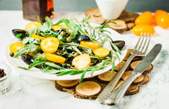 Fresh green salad with arugula, yellow tomatoes, olives, grapes. And sesame,healthy lifestyle and raw food concept Royalty Free Stock Photo