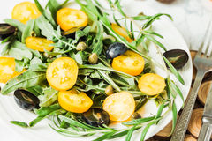Fresh green salad with arugula, yellow tomatoes, olives, grapes. And sesame,healthy lifestyle and raw food concept Stock Photography
