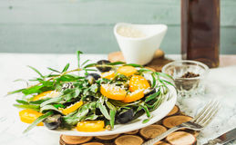Fresh green salad with arugula, yellow tomatoes, olives, grapes. And sesame,healthy lifestyle and raw food concept Stock Photo