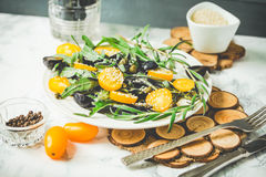 Fresh green salad with arugula, yellow tomatoes, olives, grapes. And sesame,healthy lifestyle and raw food concept Stock Image