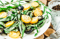 Fresh green salad with arugula, yellow tomatoes, olives, grapes Royalty Free Stock Photo