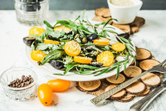 Fresh green salad with arugula, yellow tomatoes, olives, grapes Royalty Free Stock Photography