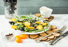 Fresh green salad with arugula, yellow tomatoes, olives, grapes. And sesame,healthy lifestyle and raw food concept Stock Photos