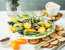 Fresh green salad with arugula, yellow tomatoes, olives, grapes. And sesame,healthy lifestyle and raw food concept Royalty Free Stock Photos