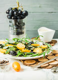Fresh green salad with arugula, yellow tomatoes, olives, grapes. And sesame,healthy lifestyle and raw food concept, selective focus Royalty Free Stock Photo